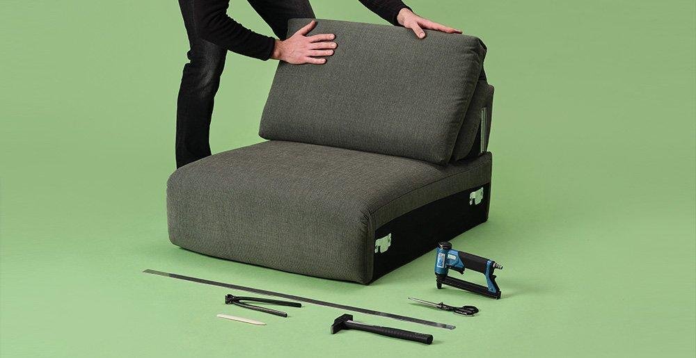 Ein Sofa-Experte verarbeitet ein Sofasitz mit dem benötigten Werkzeug.