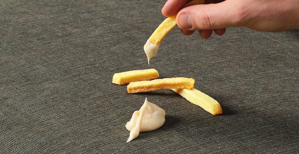 Auf dem Sofa befinden sich Pommes und Mayonnaise. Das soll zeigen wie pflegeleicht die Stoffbezüge von Sensoo sind.