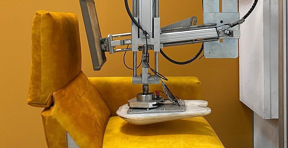 Ein Stempeltest testet hartnäckig ein gelbes Cosy1 Sofa, indem es mit einem Stempel immer wieder auf die Sitzfläche drückt.