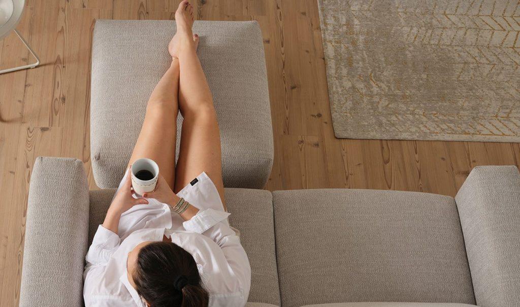 Eine junge Frau sitzt auf einem beigen Cosy1 2-Sitzer Sofa mit Hocker. Ihr Beine liegen auf dem Hocker.